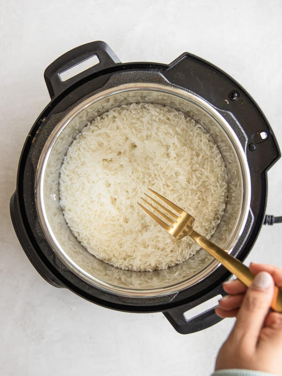 Fork fluffing cooked jasmine rice in the Instant Pot