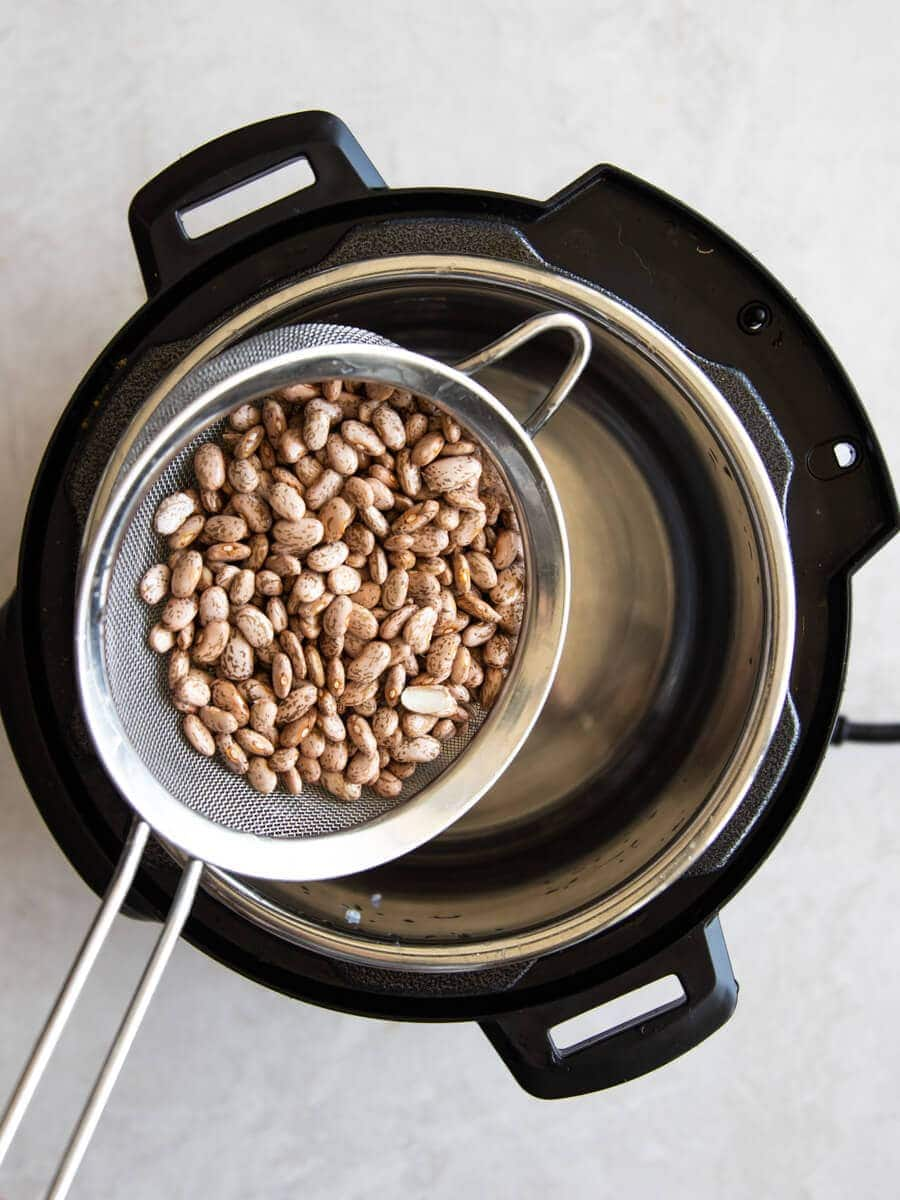 Rinsed beans in a fine-mesh sieve over Instant Pot.