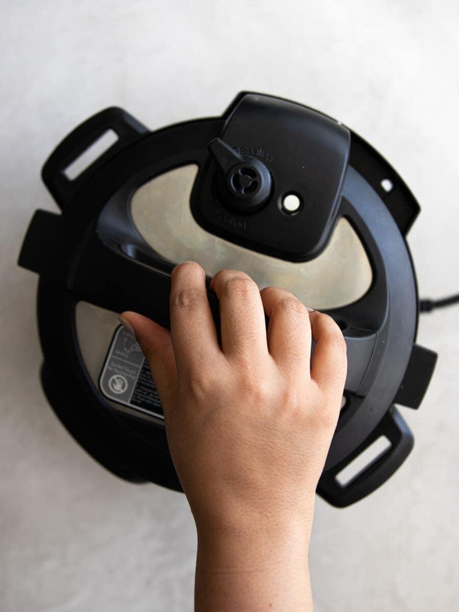 Hand closing the Instant Pot lid.