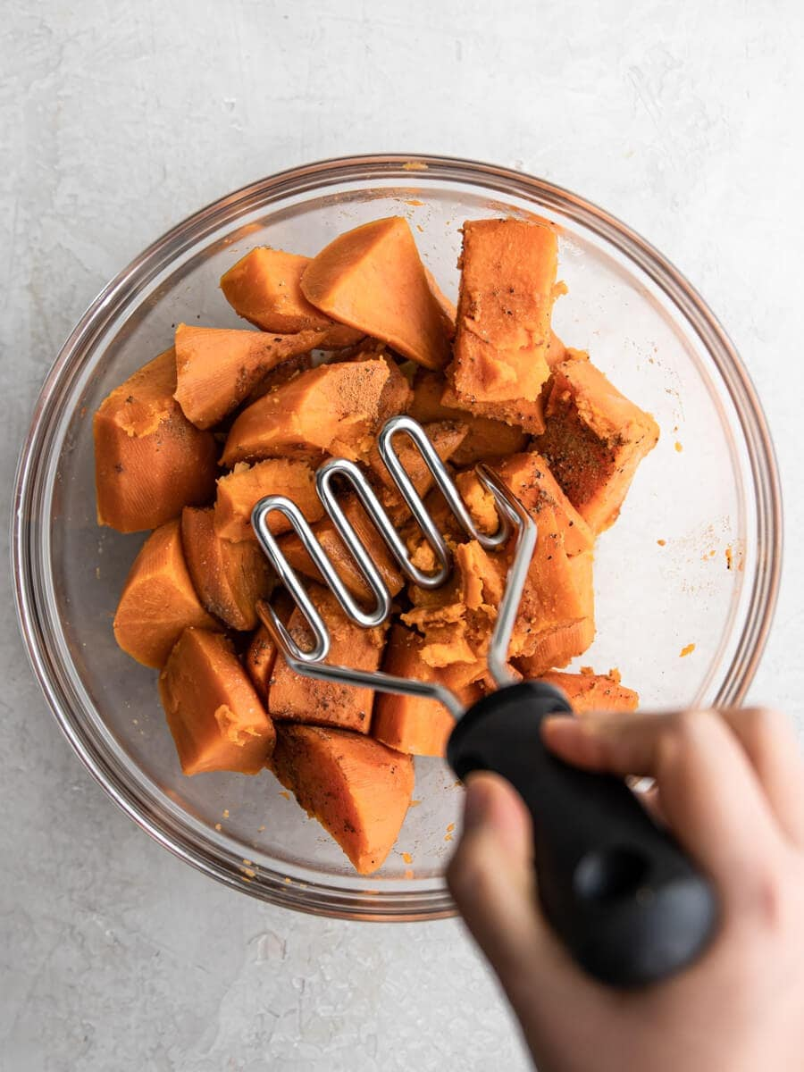 Hand mashing sweet potatoes with a potato masher