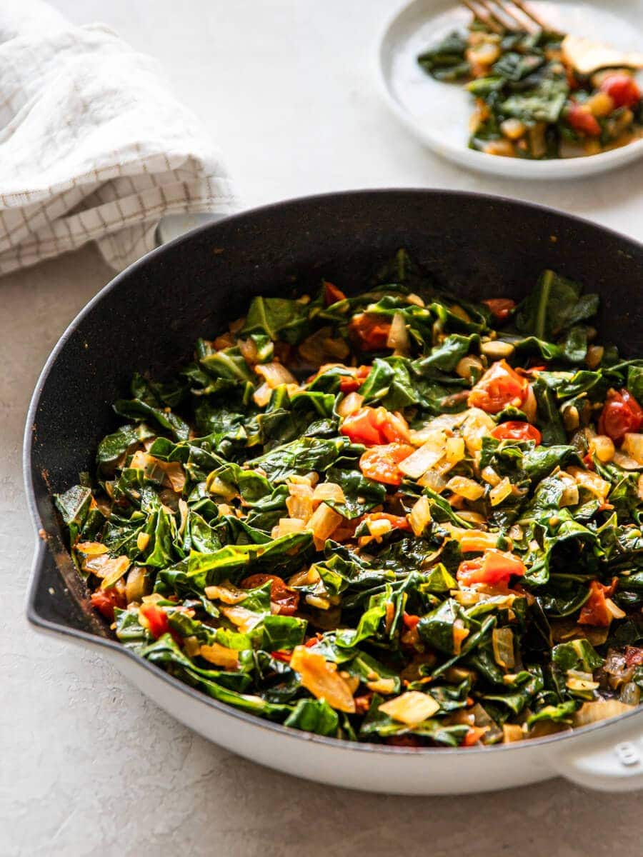 A plate of greens next to a pan of cooked greens.