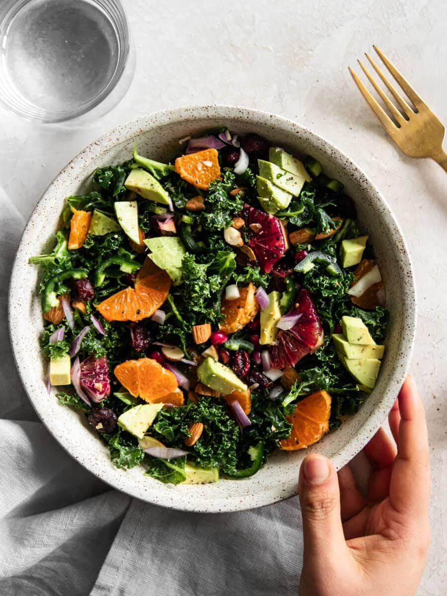 Bowl of kale salad with hand holding it.