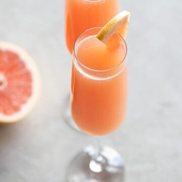 Two glasses of grapefruit mimosa with a grapefruit on the side.