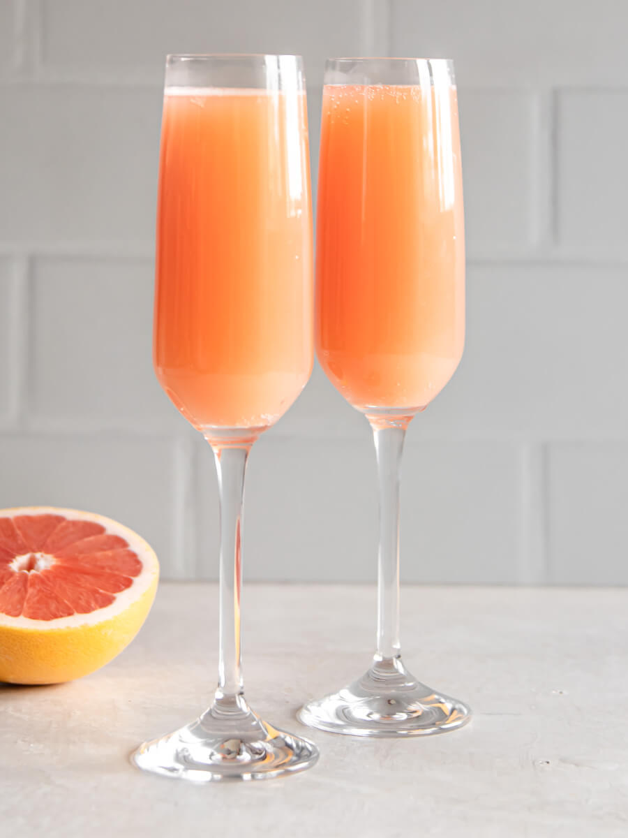 Two grapefruit mimosas next to a sliced grapefruit.