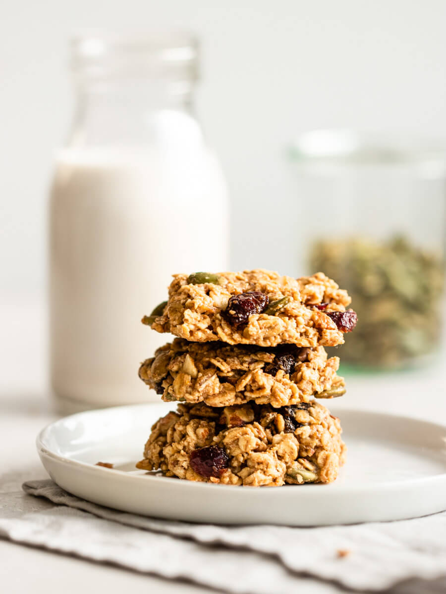 A stack of breakfast cookies with a glass of milk.