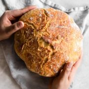 Hands holding baked bread.