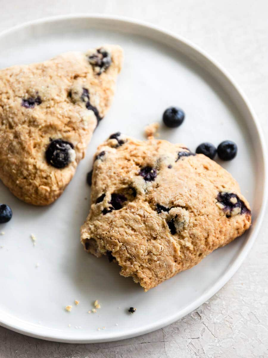 Two scones on a plate with fresh blueberries.