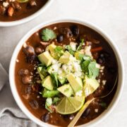 A bowl of black bean soup with toppings.