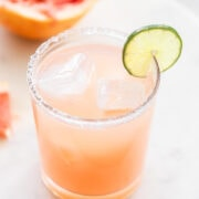 A grapefruit margarita with a slice of lime on the rim.