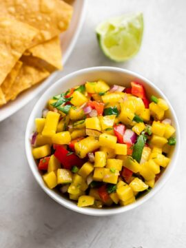 Bowl of mango salsa and chips on the side.