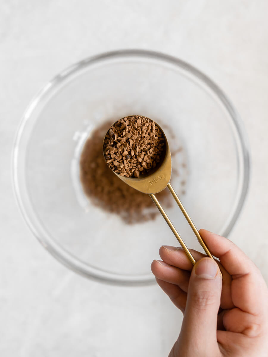 Hand holding tablespoon of instant coffee.