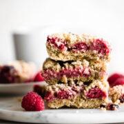 A stack of three raspberry crumble bars.