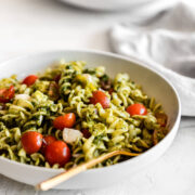 Side view of bowl of pesto pasta salad.