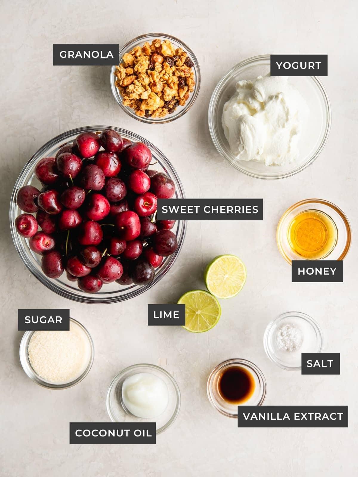 Ingredients of bowl, including cherries, granola, yogurt, honey, lime, salt, vanilla, oil, and sugar.